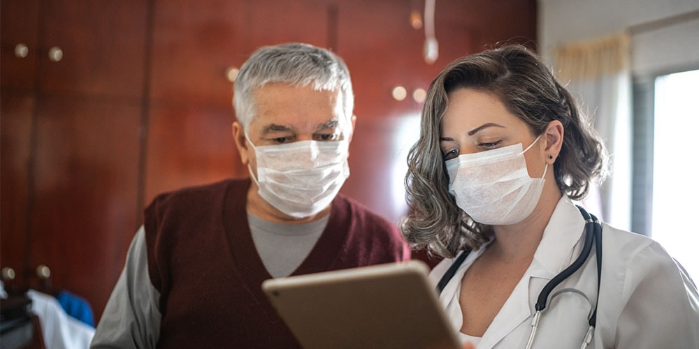 Healthcare worker and patient looking at an iPad