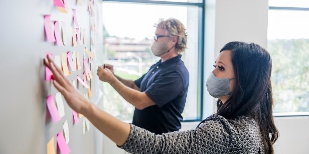 Two business people in masks pinning post-its to a wall